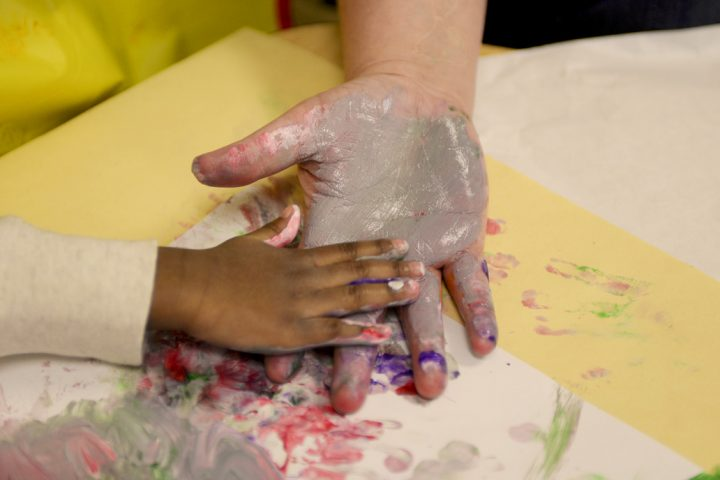 Adult and child hands covered in paint