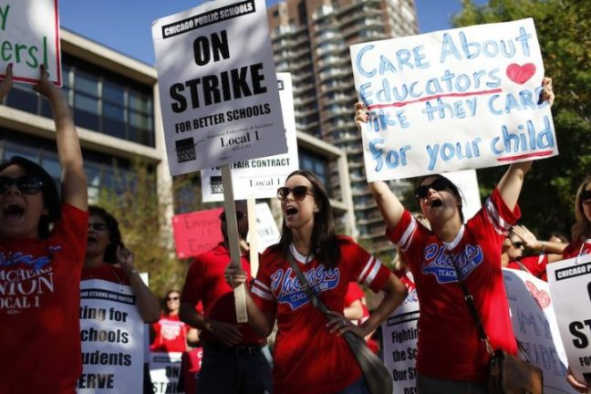 Teachers holding picket signs.