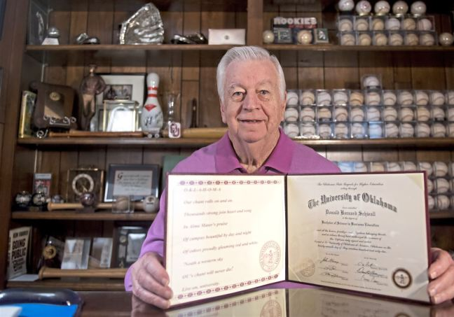 Don Schwall poses with his college degree in his home office Thursday.